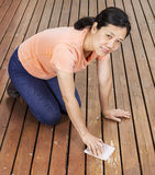 Matue woman sanding natural cedar wooden deck by hand Stock Photo
