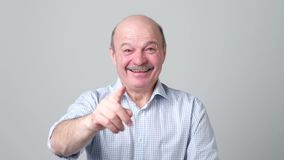 Mature adult man laughing looking at the camera. Positive emotion concept. Mature adult bald man in shirt with moustache laughing looking at the camera over stock video footage