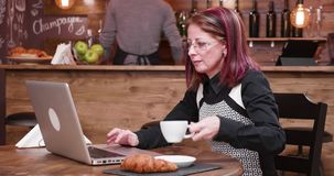 Mature and adult businesswoman in her 40s replyes to an email. While drinking coffee in vintage and stylish pub, coffee shop or restaurant stock video