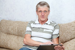 Mature adult Caucasian working with tablet pc Stock Images