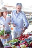 Mature adult couple buying fresh organic vegetables in a local marketplace stock image