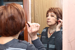 Mature adult doing make-up Royalty Free Stock Images