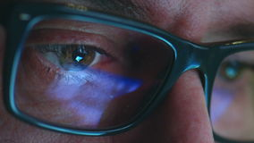 Mature adult man with glasses who works at night. Close up shot, reflections