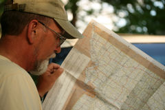 Mature adult man looking at map. Mature adult male reading map while on vacation Stock Photography