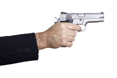 Aiming the Gun. A mature adult man wearing a suit, holding a 9mm gun with both hands aiming it to the target Stock Photo