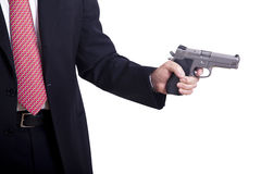 Aiming the Gun. A mature adult man wearing a suit, holding a 9mm gun with both hands aiming it to the target Stock Photography