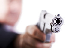 Aiming the gun. A mature adult man wearing a suit, holding a 9mm gun with his right hand, aiming it diagonally to the right Stock Photo