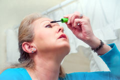 Mature Adult Woman Applying Mascara Royalty Free Stock Image