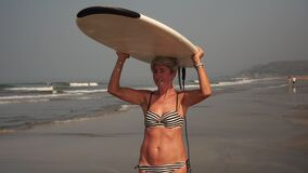 Mature adult woman on the beach holds a surfboard. Grandma is a surfer