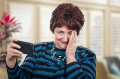 Mature adult woman is confused with mobile phone Royalty Free Stock Images