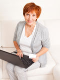 Mature adult woman with credit card and laptop Stock Photos
