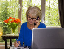 Mature adult woman working with laptop and papers in home office. Stock Image
