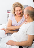 Mature adults lying in family bed. Positive mature caucasian adults lying in family bed and smiling Royalty Free Stock Images