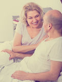 Mature adults lying in family bed. Positive mature caucasian adults lying in family bed and smiling Stock Images