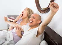 Mature adults lying in family bed Royalty Free Stock Photos