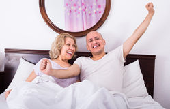 Mature adults lying in family bed Stock Images