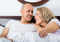 Mature adults lying in family bed Stock Photos