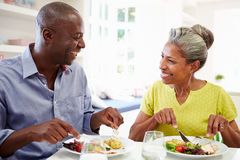 Mature African American Couple Eating Meal At Home. In Kitchen Whilst Smiling At Each Other royalty free stock images