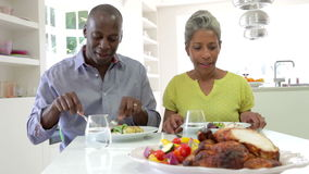 Mature African American Couple Eating Meal At Home. Mature African American couple sitting at table enjoying meal together.Shot on Canon 5d Mk2 with a frame rate stock video