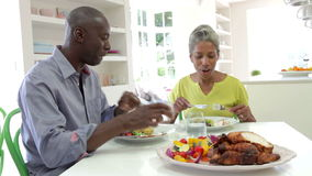 Mature African American Couple Eating Meal At Home. Mature African American couple sitting at table enjoying meal together.Shot on Canon 5d Mk2 with a frame rate stock video footage