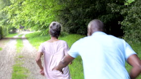 Mature African American Couple Running Along Country Path. Man runs after woman along country track before catching her and giving her hug.Shot on Canon 5d Mk2 stock footage