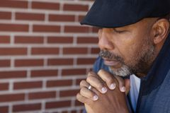 Mature African American man in deep thought. African American man standing alone looking sad Royalty Free Stock Photo