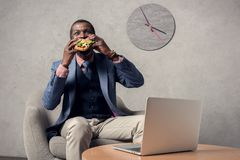 Mature african american man eating hamburger at table. With laptop stock image