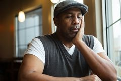 Portrait of a mature African American man in deep thought. Mature African American man sitting in a coffee shop Stock Photos