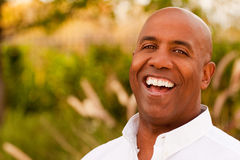 Mature African American man smiling sitting outside. Royalty Free Stock Photos