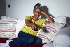 Mature African American Woman On Sofa Watching TV Royalty Free Stock Photography