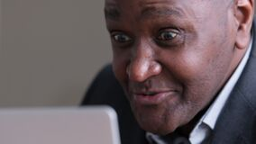 Mature African business man using laptop for video call speaks remotely emotionally. Close-up afro male wrinkled black
