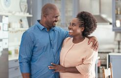 Mature African couple standing affectionately together in their kitchen. Affectionate African couple smiling and looking at each other while standing arm in arm Stock Photo