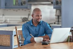 Mature African man browsing online with a laptop over breakfast. Smiling mature African man browsing online with a laptop while sitting at his kitchen table Royalty Free Stock Photos