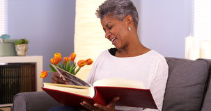 Mature African woman looking through photo album stock photography