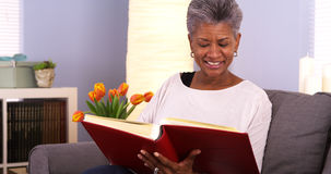 Mature African woman looking through photo album Stock Photos