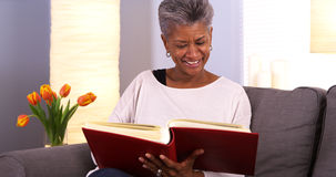 Mature African woman looking through photo album Royalty Free Stock Image