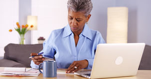Mature African woman paying her bills Stock Images