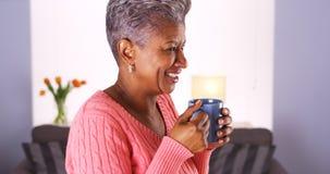 Mature African woman smiling with coffee mug Imagen de archivo libre de regalías