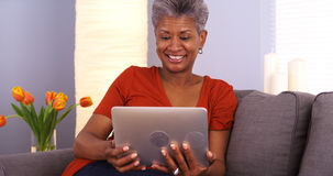 Mature African woman smiling and using tablet Royalty Free Stock Image