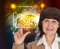 Mature age good looking woman in jacket point in finger up against neon background. Idea concept Stock Photos