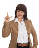Mature age good looking woman in jacket point in up.  Royalty Free Stock Photos
