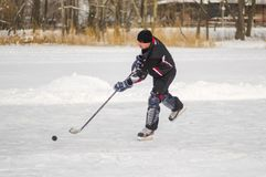 Mature amateur men playing hockey on a frozen river Dnepr in Ukraine Royalty Free Stock Photo