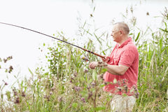 Mature angler catching fish on lake Stock Images