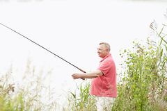 Mature angler catching fish on lake Stock Photography