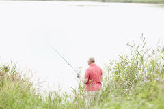 Mature angler catching fish on lake Royalty Free Stock Photos