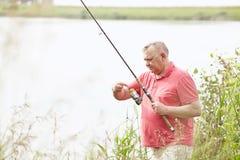 Mature angler on lake Royalty Free Stock Photography