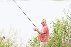 Mature angler on lake. Portrait of smiling middle aged man wearing polo shirt, angling with rod and spinning reel on summer lake - fishing concept stock image