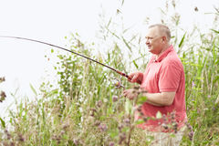 Mature angler on lake. Portrait of smiling middle aged man wearing polo shirt, angling with rod and spinning reel on summer lake - fishing concept stock photo