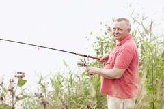 Mature angler on lake. Portrait of smiling middle aged man wearing polo shirt, angling with rod and spinning reel on summer lake - fishing concept stock images