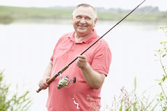 Mature angler on lake. Portrait of smiling middle aged man wearing polo shirt, angling with rod and spinning reel on summer lake - fishing concept royalty free stock images